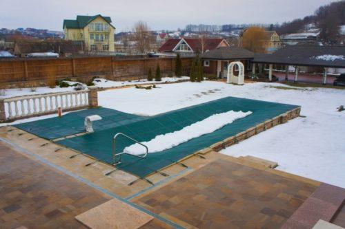 батутное покрывало укрывает бассейн на зиму